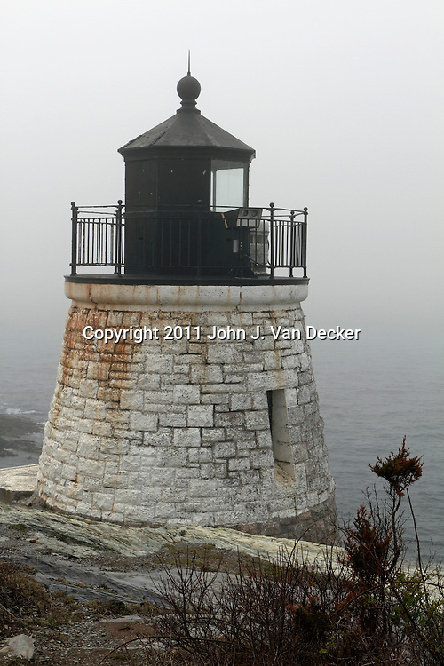 Castle Hill Lighthouse on a foggy day, Newport, Rhode Island, USA. The Castle Hill Lighthouse sits on the eastern shore marking the entrance to Narragansett Bay.
