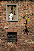 "Sculpture of a woman looking out of a window signed P.L.Olla '95 in the Bruco district or ""contrada"" of Siena. Bruco is one of the 17 Contrada's that race ine famous annual Palio di Siena. Each Contrada has it's own colors, banners and fanciful lamps that line the various  neighbourhood streets."