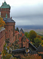 Partial view of a magnificent, red-bricked castle atop a hill in Alsace, France.