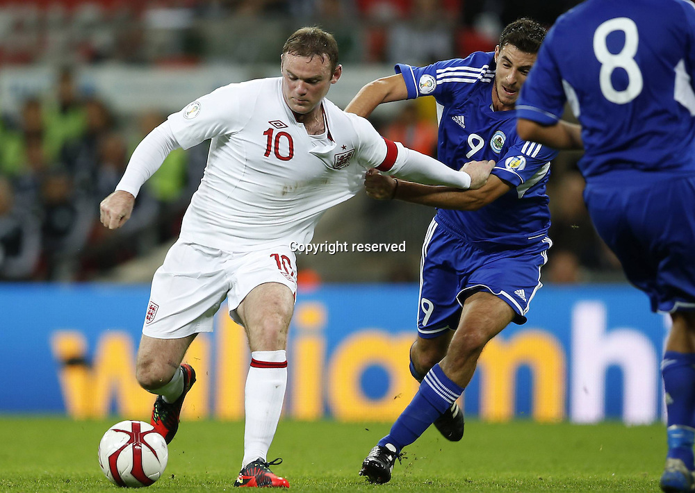 12.10.2012. Wembley Stadium, London, England.  Wayne Rooney of England challenges  with Michele Cervellini of San Marino during The FIFA 2014 World Cup Group H Qualifying Match between England and San Marino AT Wembley  Stadium. England won the game by a score of 5-0.