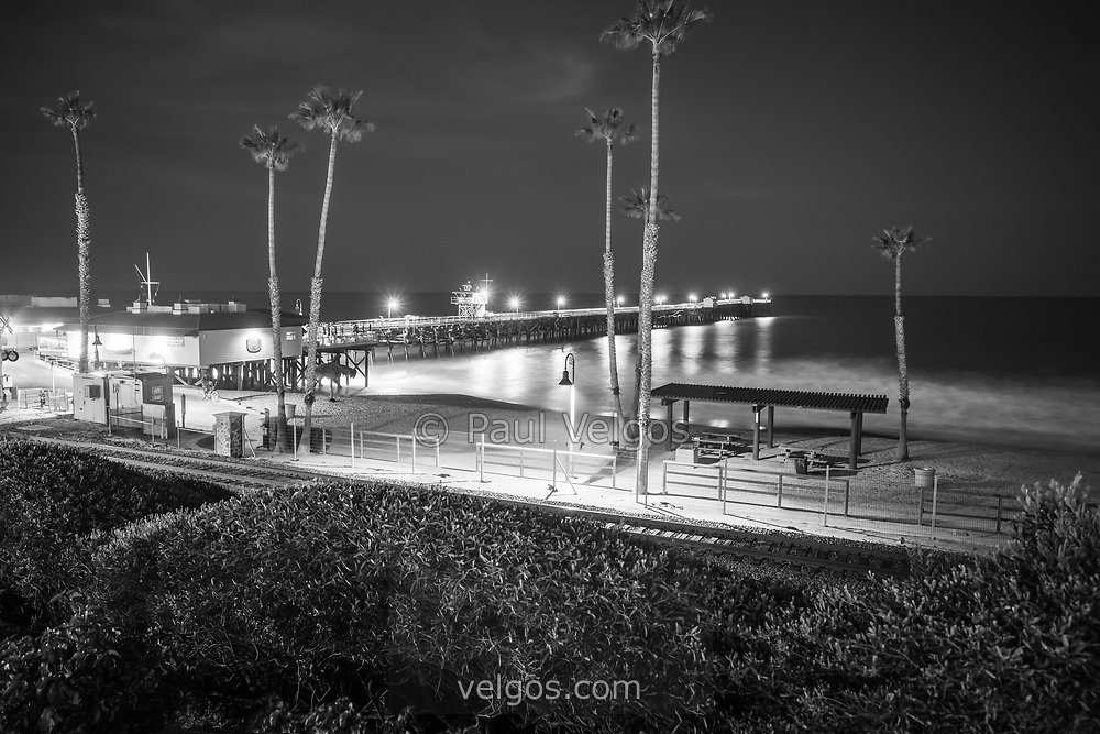 San Clemente California pier at night high resolution black and white photo. In the foreground is the San Clemente Pedestrian Beach trail and train tracks. San Clemente California is a popular coastal beach city along the Pacific Ocean n the United States of America. Copyright ⓒ 2017 Paul Velgos with All Rights Reserved.