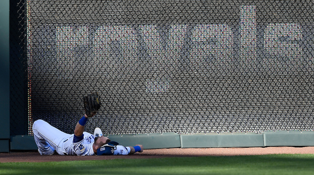 Kansas City Royals left fielder Alex Gordon held up his glove after he crashed into the wall to make a catch on a ball hit by Baltimore Orioles shortstop J.J. Hardy in the fifth inning in the American League Championship Series  playoff baseball game on October 15, 2014 at Kauffman Stadium in Kansas City, MO.