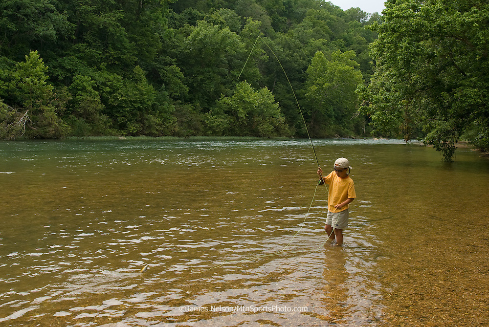 A nine-year-old boy brings a bluegill to hand while fly fishing on the James River, Missouri.