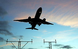 Heathrow Airport, aircraft coming into land showing runway lights in silhouette at sunrise, November 2005, Ref CHE02595d, DP NMR