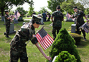 Estelle Andersen, 18, of Allenstown replaces old and damaged flags at Blossom Hill and Calvary Cemetery in Concord with the Civil Air Patrol, Concord Composite; Saturday, May 16, 2009. About thirty volunteers replaced hundreds of flags around the cemeteries. Andersen is a Chief Master Sergeant with the group.