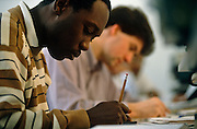 A black student works diligently alongside a white-skinned man at the communications company Cable & Wireless in London, England. We see in the foreground, the dark-skinned young man with a short beard is writing with a pencil that has a rubber on the top but the man in the background is out of focus. It is an image of ethnic diversity, of a multicultural Britain with students living and working uninterrupted side-by-side. They are both concentrating on their work in  a generic office or classroom, perhaps entering an examination or performing a corporate test.