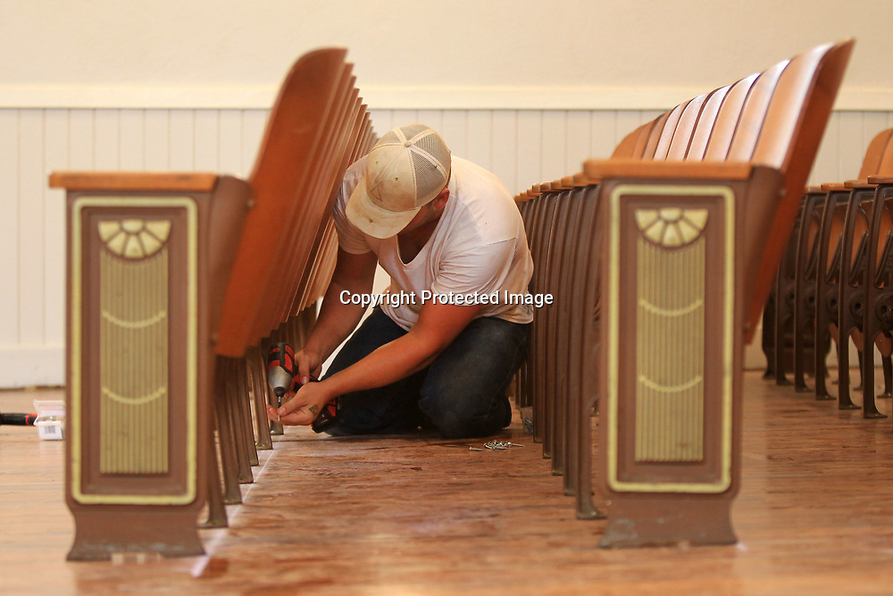Ben Bynum with Sullivan Enterprises out of Magee Mississippi, sets the screws on a row of seats being reinstalled in the auditorium at Lawhon Elementary School on Thursday morning.