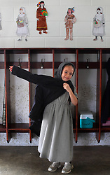 A young Amish girl puts on her coat in a one-room schoolhouse in Berlin, Ohio, Oct. 12, 2009.