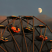 "Basking in the warm light of a setting sun, two fairgoers got a little closer look than most of a beautiful August moon from atop the ferris wheel at the Iowa State Fair midway.  The annual August event was the model for the musical, ""State Fair"", and attending the fair has been designated as ""one of the 1,000 things to do before you die."""