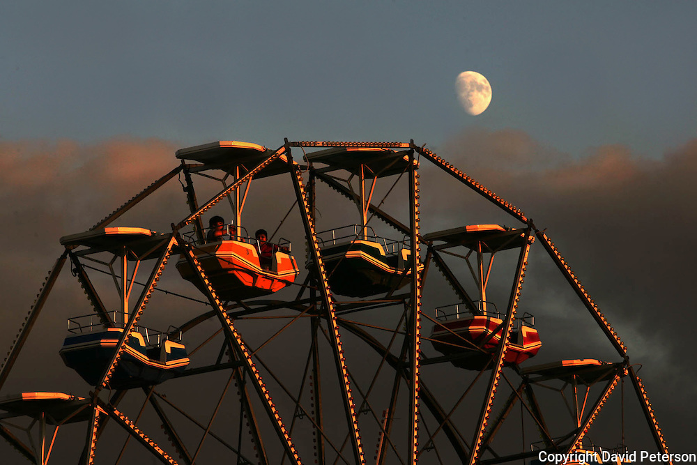 """Basking in the warm light of a setting sun, two fairgoers got a little closer look than most of a beautiful August moon from atop the ferris wheel at the Iowa State Fair midway.  The annual August event was the model for the musical, """"State Fair"""", and attending the fair has been designated as """"one of the 1,000 things to do before you die."""""""