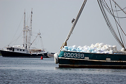 26 May 2010. Barataria Bay, Louisiana. <br /> From Barataria Bay to Grand Isle. Shrimp boats, ordinarily skimming the bay for shrimp are loading boom these days to try and keep the oil at bay. The environmental and economic impact is devastating with shrimp boats tied up, vacation rentals and charter boat fishing trips cancelled the only business for shrimpers is loading and laying boom and working for big oil. Oil from the Deepwater Horizon catastrophe is evading booms laid out to stop it thanks in part to the dispersants which means the oil travels at every depth of the Gulf and washes ashore wherever the current carries it. <br /> Photo credit; Charlie Varley<br /> www.varleypix.com