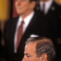 Former Chief of Staff, Treasury Secretary and Secretary of State James Baker with President Ronald Reagan in the background in February 1984 at the White House.