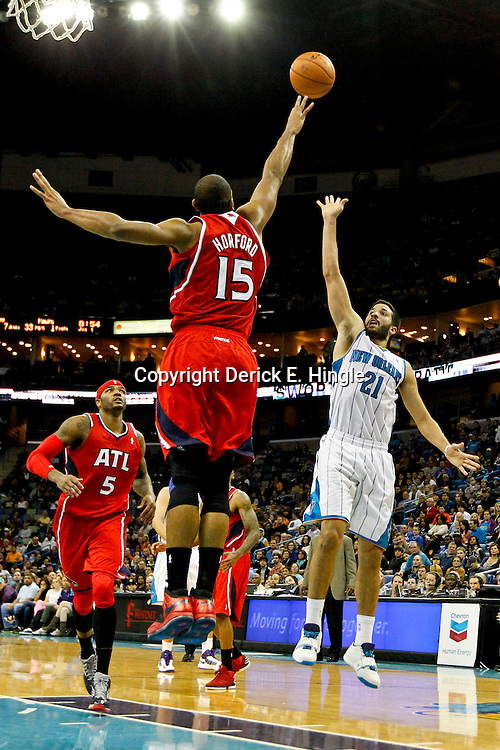 Jan 1, 2013; New Orleans, LA, USA; New Orleans Hornets point guard Greivis Vasquez (21) shoots over Atlanta Hawks center Al Horford (15) during the second half of a game at the New Orleans Arena. The Hawks defeated the Hornets 95-86. Mandatory Credit: Derick E. Hingle-USA TODAY Sports