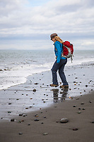 A woman playing with the waves on a beach. Dungeness Spit, Washington, USA.