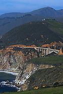 Carrying Highway 1 over a small coastal canyon along the California coast, a concrete arch bridge rises over the rocky coast line.
