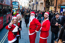 London, December 6th 2014. Tens of thousands throng the streets of London as shoppers take advantages of ongoing deals and discounts offered by retailers in the run-up to Christmas. PICTURED: A group of Santas on Oxford Street.