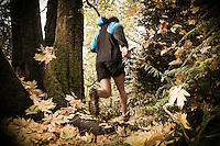 Low angle rear view of a man trail running in fall colors.