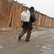 Mongolia. Ulaanbaatar. water duty inYurt city. the capital is expanding. the families  leaving in the countryside are creating huge yurts area , daily life in winter; in slums  Ulan Baatar -     /  yourte ville, l'exode rural a entraine la creation d'immenses quartiers de yourtes habites par les familles qui ont quitte la campagne. vie quotidienne en hiver dans ce qui ressemble a des bidonvilles  Oulan Bator - Mongolie   /  L0055849B