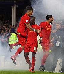 LIVERPOOL, ENGLAND - Monday, December 19, 2016: Liverpool's Sadio Mane celebrates scoring the winning goal against Everton in injury time to seal a 1-0 victory with team-mates Roberto Firmino and Emre Can, as smoke from a flare billows across the pitch, during the FA Premier League match, the 227th Merseyside Derby, at Goodison Park. (Pic by David Rawcliffe/Propaganda)