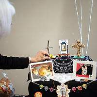 Linda Popelish puts the finishing touches on her ofrenda for the Día de los Muertos alter competition Friday at the El Morro Event Center.