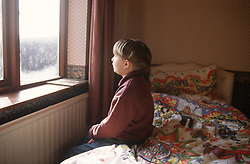 Young boy sitting on edge of bed in bedroom looking out of window,