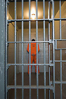 Prisoner standing in prison cell