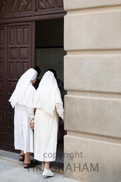 Roman Catholic nuns wearing traditional habit on their way to Mass in Segovia, Spain