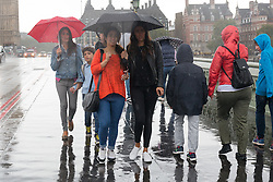 © Licensed to London News Pictures. 20/08/2016. LONDON, UK.  Tourists are caught in a heavy rain shower in Westminster in London today. Following the UK's mini heatwave this week, weather forecasters have issued a severe weather warning, predicting a spell of wet and stormy weather across the country.  Photo credit: Vickie Flores/LNP