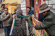 A shopper checks a vendor's wears in the market of Zado, Tibet (Qinghai, China).