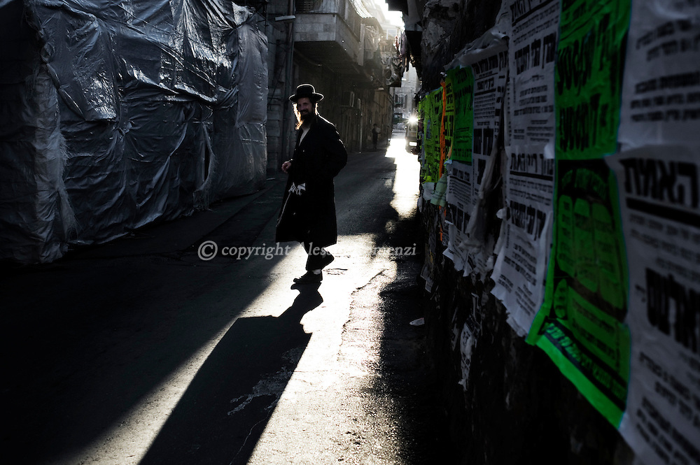 JERUSALEM : An Ultra-Orthodox Jewish man walks during the Kaparot ceremony in Mea Shearim neighborhood of Jerusalem on October 6, 2011. The Jewish ritual is supposed to transfer the sins of the past year to the chicken, and is performed before the Day of Atonement, or Yom Kippur, the most important day in the Jewish calendar, which this year will start on sunset on October 7. ALESSIO ROMENZI