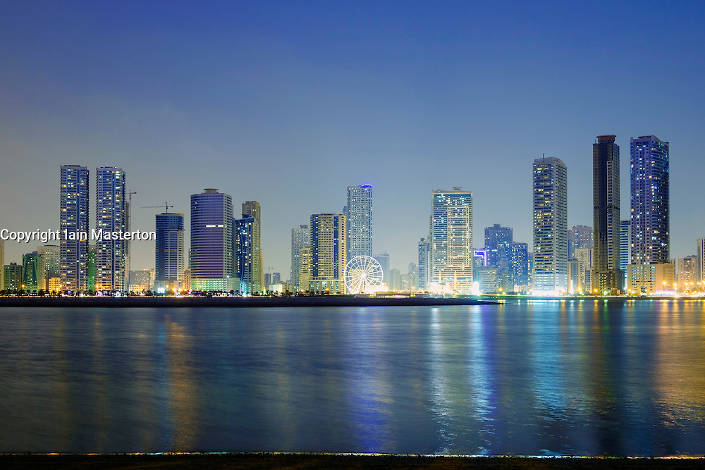 Night skyline view of beach and modern high-rise apartment buildings along Corniche in Sharjah United Arab Emirates