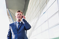 Portrait of mature attractive businessman talking on smartphone while standing at Gdansk Airport