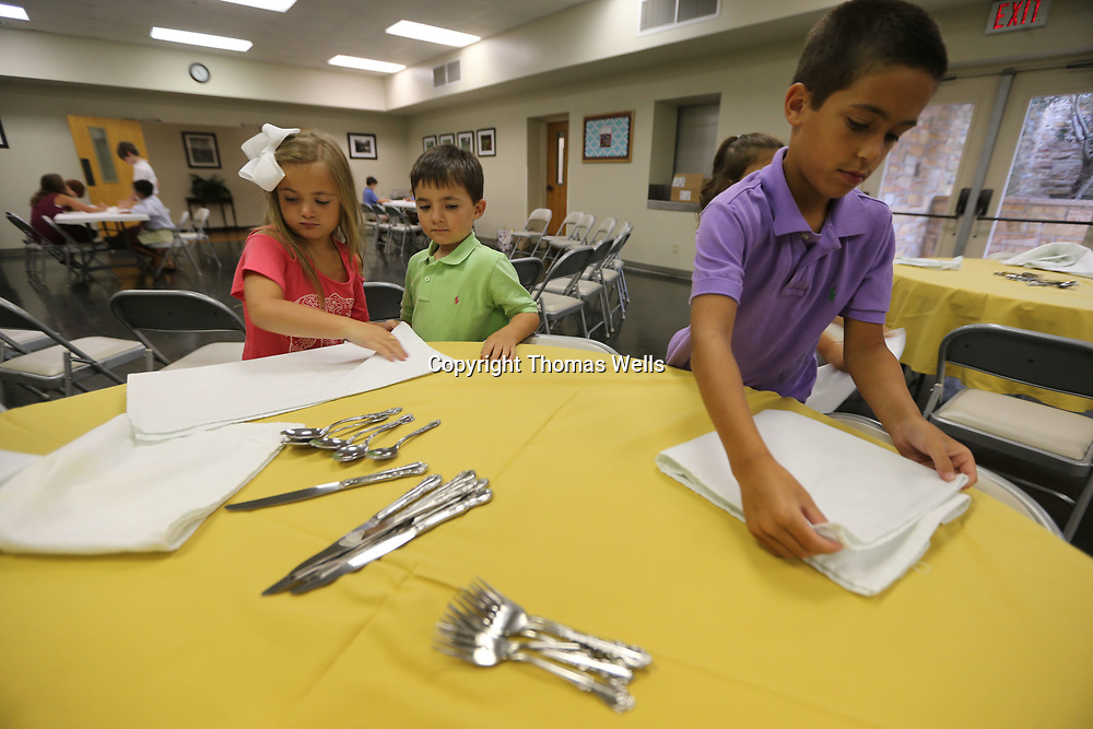 Catherine Howell, from left, and her brother, Cameron, join Bentley Oliver as they learn how to place a table as part of an etiquette Class being held at First Presbyterian Church.