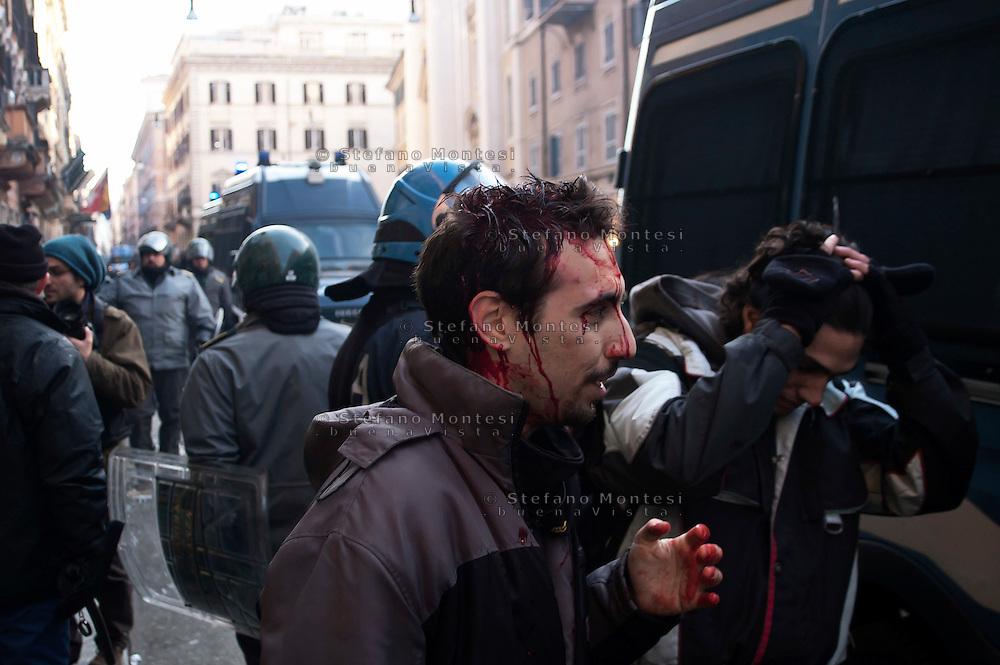 Roma 14 Dicembre 2010.Manifestazione contro il Governo Berlusconi. Manifestante ferito alla testa viene fermato dalle forze dell'ordine.