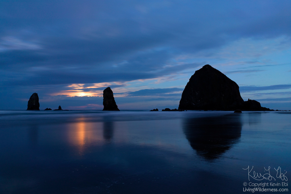 The full moon sets through a break in the clouds over Haystack Rock, located in Cannon Beach, Oregon. Haystack Rock, at 235-feet (72 meters), ranks as the world's third-tallest sea stack.