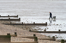© Licensed to London News Pictures. 28/02/2019. Sheerness-on-Sea, A fisherman walks back shore after checking his nets. Coats on as people say goodbye to the heatwave and hello to Cooler and cloudier weather today at Sheerness-on-sea at the Kent coast.  Photo credit: Grant Falvey/LNP