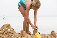 Pre-teen girl building sand castle on beach