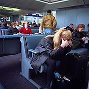 A female passenger leans forward with head in hands amid the busy terminal at Chicago O'Hare Airport, Illinois, USA. Fellow-travellers in the background appear unworried, waiting for their respective flights in a calm manner. The lady in the foreground's body language however, suggests fatigue and distress and perhaps a fear of flying. Picture from the 'Plane Pictures' project, a celebration of aviation aesthetics and flying culture, 100 years after the Wright brothers first 12 seconds/120 feet powered flight at Kitty Hawk,1903. .