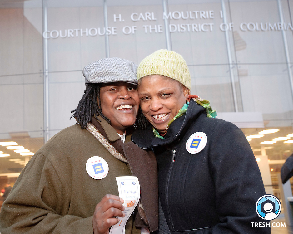 Sinjoyla Townsend, of Washington, left, and her partner Angelisa Young, pose outside of the Superior Courthouse of the District of Columbia, Washington, D.C., Wednesday, March 3, 2010, holding a ticket that keeps their place as the first same-sex couple to legally apply for a District marriage license.