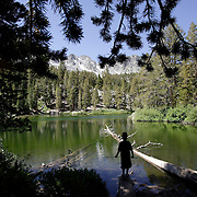 A young boy walks on a dead tree while enjoying the view from Emerald Lake during a hike in Mammoth, California.