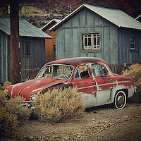 Automobile abandoned by small buildings