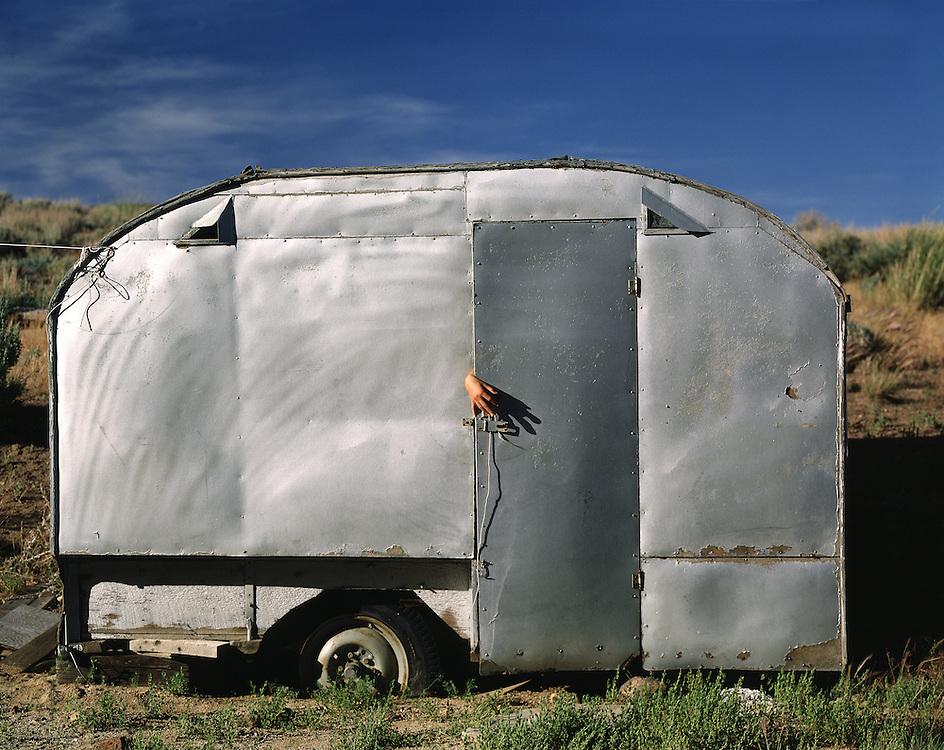 Old aluminum trailer with hand coming around door