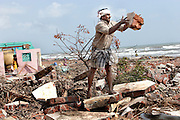 A man begins to clear the rubble that was once his house on the sea shore in Nagapattinum, most of those whose houses were destroyed don't want to live right beside the sea anymore, instead if possible opting to live a mile inland.