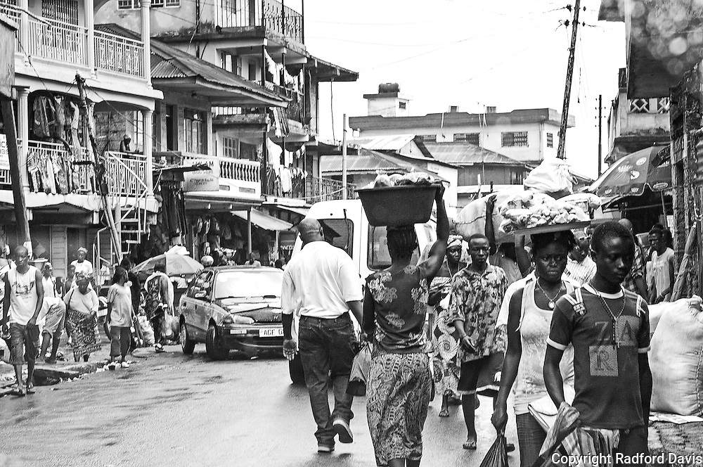 Freetown, Sierra Leone. Nearly half the population of Sierra Leone lives in Freetown. Young people move to the city from rural life in hopes of finding work and a more exciting life, but find making a living difficult. Many take to selling sundry items on the streets. Electricity is unreliable. The roads are good in some areas of the city, but many still need repair. It is estimated that nearly 60% of the country's operating budget comes from donor countries.