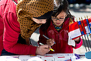 "Sharifah Nadiah helps Elmira Nabila Zafari (9) draw a Polish flag at one of the booths set up for the International Street Fair Saturday, April 20, 2013. The International Street Fair was held on Court Street from 11 a.m. to 5 p.m. during the last day of Ohio University's annual ""International Week"