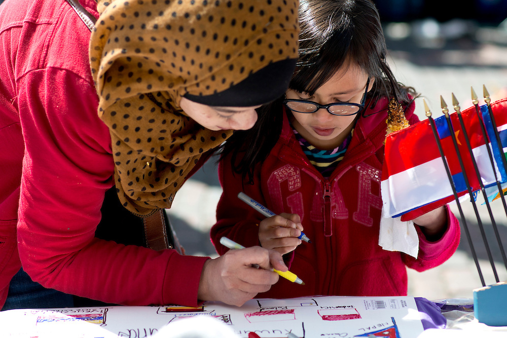"""Sharifah Nadiah helps Elmira Nabila Zafari (9) draw a Polish flag at one of the booths set up for the International Street Fair Saturday, April 20, 2013. The International Street Fair was held on Court Street from 11 a.m. to 5 p.m. during the last day of Ohio University's annual """"International Week"""