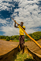 Dassanach tribe man rowing a dugout canoe called a tankua across the Omo River,, Omo Valley, Ethiopia.
