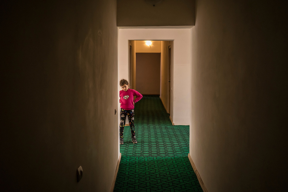 A girl who was displaced along with her family by recent fighting in the city of Martakert stand in the hallway of a hotel where they are temporarily being housed on Monday, May 9, 2016 in Stepanakert, Nagorno-Karabakh.