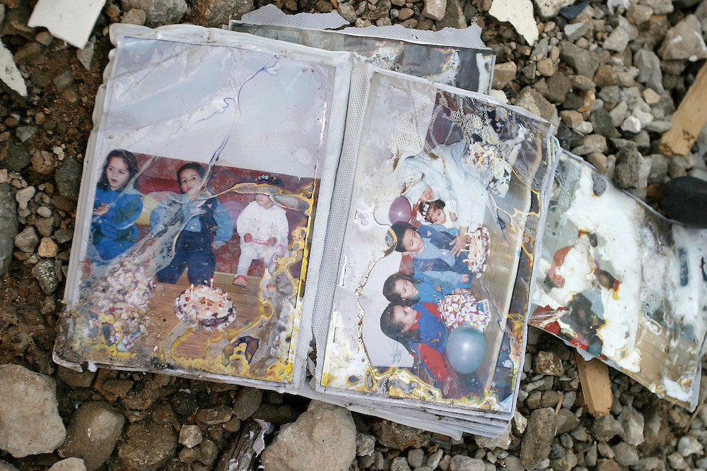Birthday snapshots lie in the rubble of a flattened apartment complex 