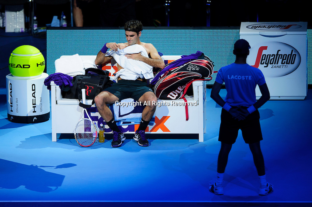 12.11.2012 London, England. Switzerlands Roger Federer changes his shirt inetween games as he plays Serbias Novak Djokovic during the Final of the Barclays ATP World Tour Finals at The O2 Arena.